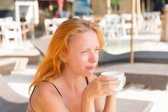 在海滩的少妇饮用的咖啡 免版税库存图片
