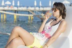 在海滩的少妇饮用的鸡尾酒画象  免版税库存照片