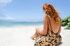 在海滩的少妇读书 图库摄影