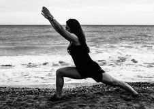 在海滩的少妇去的瑜伽在清早 库存照片