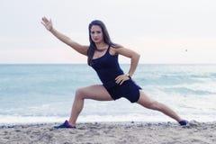 在海滩的少妇去的瑜伽 免版税库存图片
