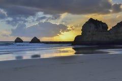 在海滩的岩石在日落 库存图片