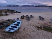 在海滩的岸的蓝色小船 库存照片