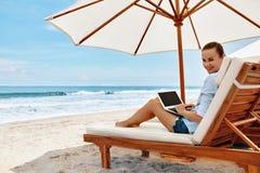 在海滩的工作 研究在网上膝上型计算机的女商人户外 免版税库存图片
