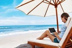 在海滩的工作 研究在网上膝上型计算机的女商人户外 库存照片
