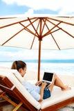 在海滩的工作 研究在网上膝上型计算机的女商人户外 免版税库存照片