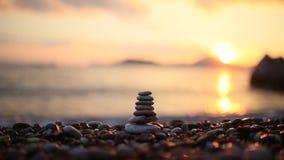 在海滩的平衡石头 给蒲公英领域开花的长发头脑和平松弛白人妇女年轻人穿衣 平衡生活 加州 股票录像