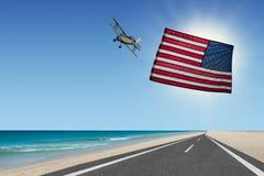 在海滩的平面飞行与美国国旗 库存图片