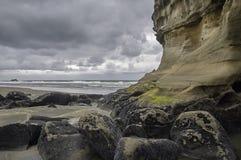 在海滩的强加的被风化的峭壁 库存照片
