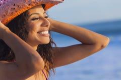 在海滩的微笑的妇女女孩比基尼泳装牛仔帽 图库摄影