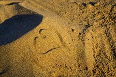 在海滩画的心脏在日落期间 库存照片