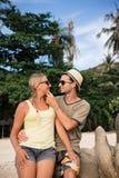 在海滩的愉快的夫妇在日落 库存图片