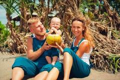 在海滩的愉快的家庭野餐 母亲,父亲饲料男婴 免版税库存照片