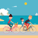 在海滩的愉快的家庭骑马自行车 免版税图库摄影