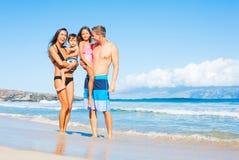 在海滩的愉快的混合的族种家庭 库存图片