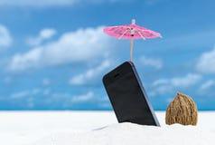 在海滩的手机和鸡尾酒伞 免版税库存图片
