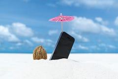 在海滩的手机和鸡尾酒伞 图库摄影