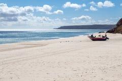 在海滩的搁浅的小船Salema (阿尔加威,葡萄牙) 库存照片