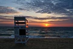 在海滩的救生员椅子在日出 免版税库存照片