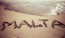 在海滩的文本马耳他 图库摄影