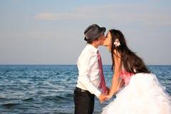 在海滩的新娘和新郎 免版税库存照片