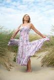 在海滩的无忧无虑的老妇人跳舞 免版税库存照片