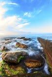 在海滩的日出与岩石和海 免版税库存图片