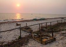 在海滩的日出与狗和渔船 库存照片