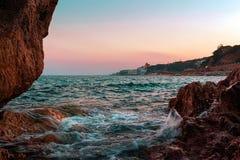 在海滩的日出在巴塞罗那,卡塔龙尼亚,西班牙附近的卡莱利亚 免版税库存照片