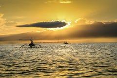 在海洋的日出在Lovina海滩,巴厘岛附近 渔夫小船我 图库摄影