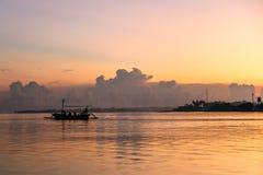在海洋的日出在Lovina海滩,巴厘岛附近 渔夫小船我 免版税图库摄影