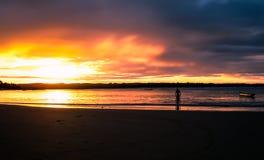 在海滩的日落与一个人和小船 免版税库存图片