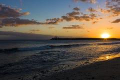 在海滩的日落与在峭壁的一座风景灯塔 免版税图库摄影