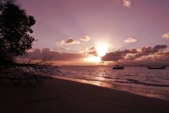 在海滩的日落与在海的小船 免版税库存照片