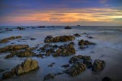 在海滩的日落与岩石小岛 免版税库存图片