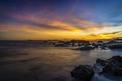 在海滩的日落与岩石小岛 库存照片