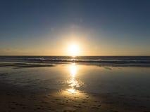 在海滩的日落与强烈发光橙色,黄色,红色col 免版税库存照片