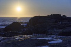 在海滩的日落与某一海岸晃动 免版税库存图片