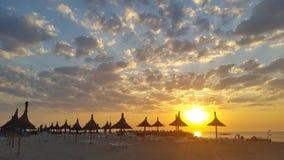 在海滩的日落与芦苇伞 免版税图库摄影
