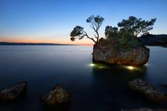 在海滩的日落与Kamen Brela (Brela石头), Brela,亚得里亚 免版税库存照片