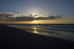 在海滩的日落云彩 库存图片