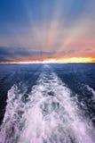 在海洋的日落有小船苏醒的 免版税库存图片