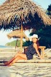 在海滩的日落期间年轻美丽的女孩愉快的画象有帽子的在竹子sunbed 库存图片