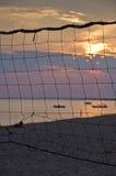 在海滩的日落通过排球网 库存照片