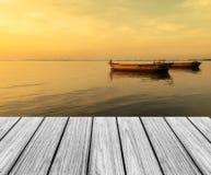 在海滩的木大阳台与与大小船的日落 免版税库存图片
