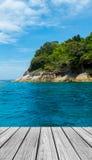 在海滩的木大阳台与清楚的天空、蓝色海和海岛 免版税库存照片