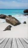 在海滩的木大阳台与清楚的天空、蓝色海和海石头 免版税图库摄影