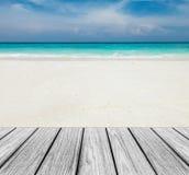 在海滩的木大阳台与清楚的天空、蓝色海和白色沙子对输入文本 图库摄影