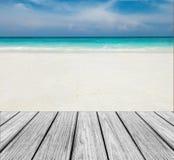 在海滩的木大阳台与清楚的天空、蓝色海和白色沙子对输入文本 免版税图库摄影