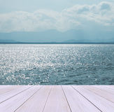 在海滩的木大阳台与清楚的天空、水晶干净和清楚的来到跳船嘲笑的风景背景的海和大波浪  免版税库存照片